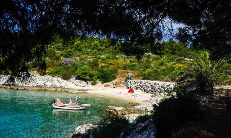 Zelt und Boot am einsamen Strand in Kroatien