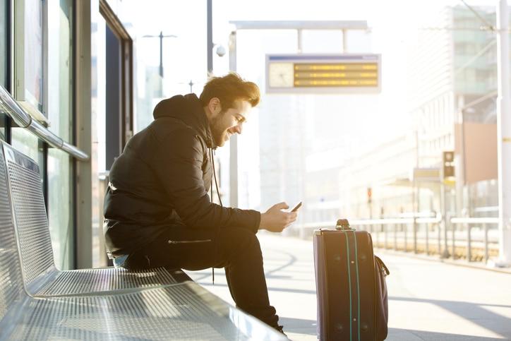 Junger Mann wartet mit Gepäck am Bahnhof