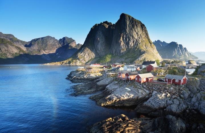 Eine typisch skandinavische Holzhütte an einem der zahllosen wie gemalt wirkenden Fjorde ist die perfekte Kulisse für einen romantischen Norwegen-Urlaub.