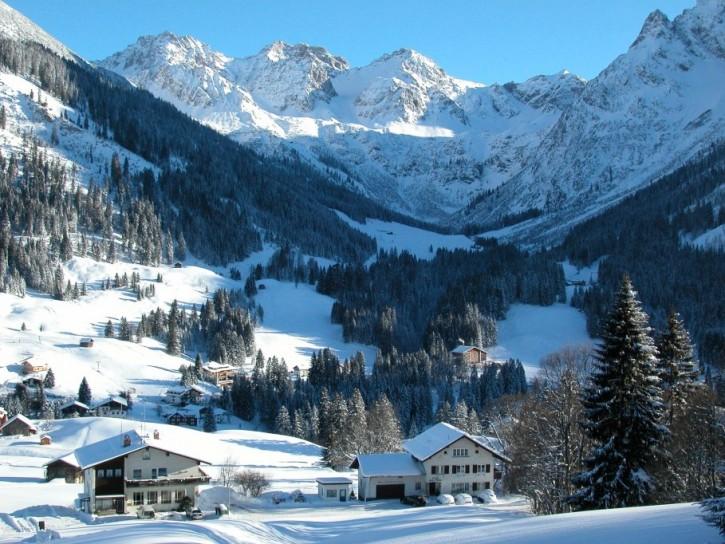Das Ferienhaus Ahorn (vorne rechts) in Mittelberg empfängt bis zu 20 Personen im Herzen des Allgäuer Winterwunderlands.