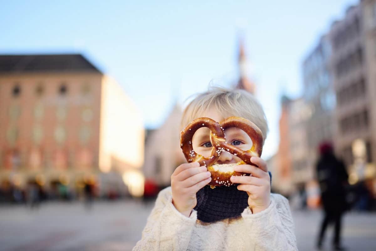 Junge isst Brezel auf dem Marienplatz